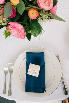 Summer wedding place setting idea - white plates with navy blue napkins and bright, floral centerpieces {Riverland Studios}