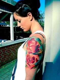 "Not your typical ""I'm 18 so I'm going to get a rose tattoo"". Exquisite colors brighten the realistic rose tattoos shining from her upper arm."