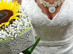 Sunflower and baby's breath in a cube-like lace trimming.