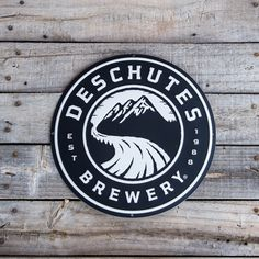 "From Beer Town USA comes this round Deschutes Brewery logo tin tacker.  Embossed and matted (meaning not shiny), approximately 12"" in diameter."