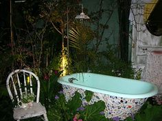 For those who like the unusual and recycled, here is a bathtub with mosaic work on the sides. Note the shower head delivers the water to the tub. This would be great for the eclectic garden.