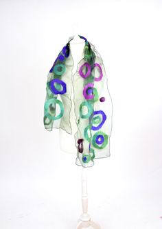 Sheer felted scarf made from silk and wool with loads of diffferently sized circles on it. Its made from organza so it looks more structured and volumnous on your neck!