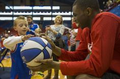 Kansas University freshman guard Andrew Wiggins smiles as 7-year-old Jaden Dallen, of Overland Park, shows him where to autograph his basketball, Saturday, Dec. 28, 2013, at Allen Fieldhouse. Members of the KU men's basketball team met with fans and led drills during their annual holiday clinic. #KU