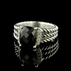 This David Yurman Sterling Silver Onyx and Diamond Wheaton Ring is set with a faceted cushion shaped onyx flanked by ten full cut diamonds.