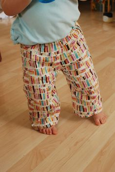Book pants -- These adorable, comfortable cloth diaper pants feature a print from the Victoria and Albert museum collection of fabrics, with teal, pink, and brown book spines
