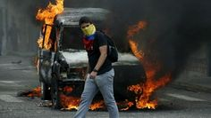 A demonstrator wearing a Venezuelan national flag to cover his face walks in front of a burning van during a protest against President Nicolas Maduro's government in San Cristobal, Venezuela, March 3, 2016. | Foto: Reuters