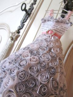 This adorable paper rose covered, ballroom style dress miniature is made from book pages.  It is carefully stitched in pink cotton with pale pink trim for straps.  Two ribbons, one of spotted pink satin overlayed with another of organza with pale pink swirls create the belt, which is adorned with a sparkly diamante metal buckle.