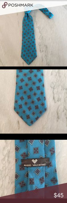 "Mario Valentino 100% Silk Neck Tie Authentic Mario Valentino Men's Neck Tie. This Tie is in perfect condition beautifully made. Turquoise Blue background makes this Tie perfect for the summer months to come. 54""L 4""W Mario Valentino Accessories Ties"
