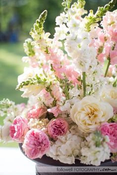 Idea for wedding chapel arrangement- add bells of Ireland to snapdragons for height. Replace majority of roses with dahlias in shades of pink and white. Annelise prefers this because the chapel is round.