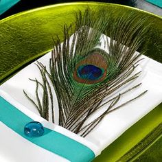 "Fold simple white napkins into ""pockets"" and tuck a peacock feather into each pocket. Decorate the napkin with a band of ribbon and hot-glue a jewel-tone gem or large crafts rhinestone in the center of the band."
