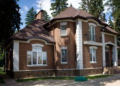 Вариант кирпичного загородного дома коричневого цвета в английском стиле