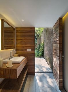 Unique bathroom design. Crisp modern shapes, minimal fixtures, warm tones from the natural materials and clean flooring style that leads out into the garden space. I love it! Bathroom heaven
