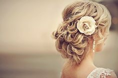 Soft, elegant bridal hairstyle with cream-colored flower. Timeless.