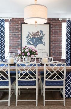 Blue dining room features a linen drum pendant hanging over a salvaged wood dining table lined with white bamboo dining chairs accented with blue cushions against a backdrop of an exposed brick wall lined with a Natural Curiosities Capistrano Seaweed 1 flanked by windows dressed in blue lattice curtains.
