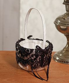 This dramatic black beaded lace on the ivory basket creates a striking effect.  Very Formal or Simply Elegant.  49.98  Available at  ajoyousaffair.net