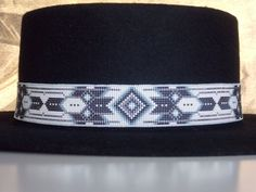 """Cherokee Black Diamond Hat Band"" Cherokee Black Diamond Native American Beaded Hat Band With The Colors Of Whit Opal And Shades of Grey by LJ Greywolf This Native American Beaded Hat Band with the Cherokee Black Diamond design is beaded with the colors of white opal, black, hematite and shades of grey. This hat band is not just jewelry for your hat but a work of art that will turn many heads when you wear it! This beaded hat band is made up of tiny glass beads that measure about 1 mm each. Using such a small bead allows me to get a large amount of detail in such a small amount of area. Each end of the beaded hat band is hand sewn to black stained leather and ties in the back with a black hand braided leather cord decorated with a sterling silver slider bead. The sterling slider bead is made by hand. I cut, shape, and polish each sterling bead by hand. Each end of the leather braid is a sterling silver tip with a horse hair tassel that I also make by hand. I cut and polish each sterling silver tip and insert horse hair into each end. I have beaded a finished edge across the top and bottom of the hat band, Within this finished edge I used a beaded thread that has 10 pounds of tensile strength. The hat band measures approximately 22 inches long and 1 inch wide. I'm sure you will enjoy wearing and showing off this beautiful American Indian hat band. This beaded hat band will make a very special gift for that someone special in your life. Each beaded hat band is shipped to you in an attractive gift box and with a certificate of Authenticity. Thank you for looking at my Cherokee beaded jewelry."