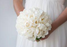 Rounded hand held bouquet featuring white double tulips and geranium foliage around the base of the bouquet.