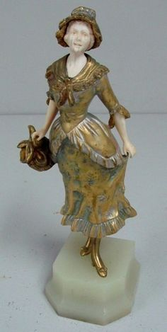 Manos - Georges Omerth ( 1895-1925) Bronze and ivory sculpture depicting a Victorian woman wearing a bonnet holding a basket mounted on onyx base. Signed Omerth and # 7526 on dress. Lines in Ivory face. Approx. 10.  Made in France Circa: 1900 Signature: Omerth Reference: Art Deco and other figures by Catley, page 248.