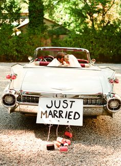 the happy couple in vintage car leaving reception with just married sign - photo by San Francisco based wedding photographer Lisa Lefkowitz