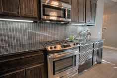 Glass backsplash, stainless steel appliances, and dark cabinets bring a rich and modern look to this kitchen.