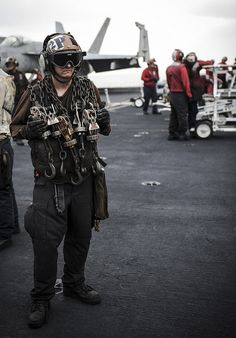 "GULF OF OMAN (July 15, 2013) - Aviation Machinist's Mate 2nd Class Forrest Sledge, a native of Zuma Beach, Calif., assigned to the ""Argonauts"" of Strike Fighter Squadron (VFA) 147, stands by with chains on the flight deck of the aircraft carrier USS Nimitz (CVN 68). Nimitz Strike Group is deployed to the U.S. 5th Fleet area of responsibility conducting maritime security operations, theater security cooperation efforts and support missions for Operation Enduring Freedom. Us Navy Aircraft, Military Aircraft, F14 Tomcat, Uss Nimitz, Go Navy, Flight Deck, United States Navy, Us Air Force, Navy Ships"