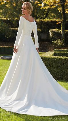 Simple ball gown wedding dress with long sleeves and bateau neckline for the modest bride | Nicole Milano Wedding Dresses 2021 Collection - Belle The Magazine #weddingdress #weddingdresses #bridalgown #bridal #bridalgowns #weddinggown #bridetobe #weddings #bride #dreamdress #bridalcollection #bridaldress #dress See more gorgeous bridal gowns by clicking on the photo