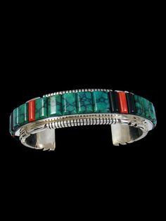 This heavy sterling silver cuff has Cloud Mountain turquoise, coral, and jet cornrow inlay. Signed and marked sterling by the artist, Thomas Francisco. Size: Fa