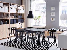 Grande salle à manger avec table et six chaises noires, avec rangements en pin massif.