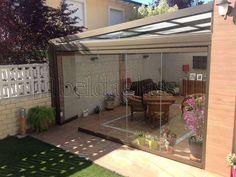 Beldaglass realiza una instalación de cerramiento de terraza con techo móvil de policarbonato y cortinas de cristal sin guía al suelo en Madrid.¡ Llámanos!
