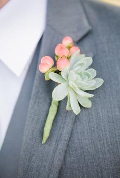 A heat-friendly boutonniere comprised of succulents and pink hypericum berries | Brides.com