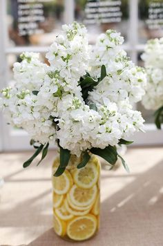 White Wedding Flowers: This unique floral arrangement has a floral vessel filled with bright yellow lemon slices that makes the arrangement so fresh.