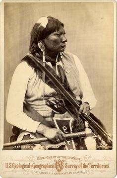 Photograph (black and white); cabinet card, studio profile portrait of Milky Way (Esa-ha- bith), a Comanche chief, seated wearing a cloth shirt, a neck tie, dentalium ear ornaments, a blanket around his waist, an eagle feather in his hair, and a fur sash; he is holding a bow and a quiver of arrows in one hand, and a tomahawk in the other; Washington DC, United States of America.  Albumen print