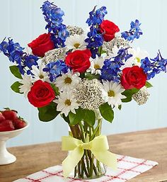 The yellow ribbon has become an icon of support for the men and women of our military, and traditionally has always symbolized the ties that bind. Show your support for someone you want to remember with our hand-designed, patriotic arrangement of red roses, blue delphinium and white daisy poms, gathered in a stylish glass vase tied with a symbolic yellow ribbon.