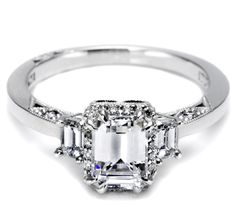 """An emerad cut diamond, set within a Dantela setting with stunning trapezoid """"flares"""" lighting it up on either side of the ring. (TACORI)"""