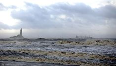 St Mary's Lighthouse is battered by rough seas and strong winds in Whitley Bay near Newcastle upon Tyne this morning