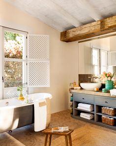 Baño con mueble oscuro, suelo hidráulico, vigas de madera, bañera y ventana_429508