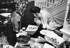 A candid photo of Jackie Kennedy staring at a portrait of her late husband, while her daughter, Caroline, opens a present.