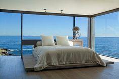 großes Bett und Glaswände im Schlafzimmer