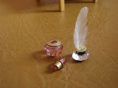 My little little dream: Making miniature inkwell and a bottle of perfume. Cut off bottom of diamond-shaped bead, drill hole the same size as rivet that will go into hole. Paint the ink color inside of hole, then glue rivet into place.