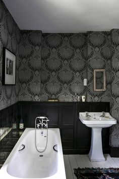 Nature inspired wallpaper is sure to create a modern rustic vibe. This bathroom's dark wainscotting perfectly compliments the wallpaper letting it shine. #RusticHomeDecor #RusticBathroom #RusticBathroomIdeas