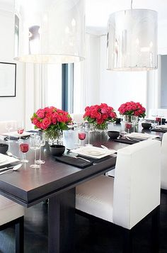 Metallic cylinder lighting over espresso brown table and white upholstered chairs in dining room