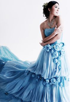 sea blue strapless dress with long train and sparkles at top of bodice and blue roses along top of separations between the skirts