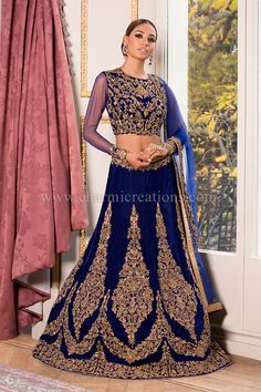 Reception Gown - Navy blue velvet lengha with bold antique gold motifs with an embroidered see-through net blouse and long-sleeved design perfect for a wedding reception event Asian Wedding Dress Pakistani, Asian Bridal Wear, Indian Wedding Outfits, Bridal Outfits, Pakistani Dresses, Indian Bridal, Indian Outfits, Indian Clothes, Indian Gowns