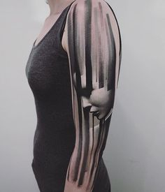 Black paintbrush stripes and face tattoo inked on the left sleeve