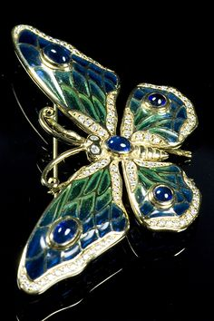 An 18ct yellow gold mounted butterfly brooch with blue/green enamel wings with cabochon sapphire and round brilliant cut diamond accents on the body and wings. Stamped NB for Nicole Barr Hallmarked 750. Edinburgh.