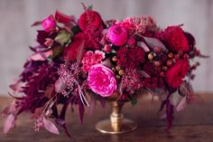 Other tables will have a gold compote vase spilling with burgundy peonies, burgundy dahlias, deep red spray roses, burgundy succulents, and burgundy seeded eucalyptus surrounded by gold mercury glass votives.
