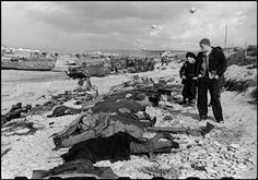 FRANCE. 1944. Normandy. Omaha Beach. French fishermen looking at the bodies of soldiers killed.