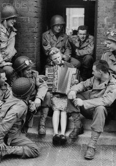 Mrs. Hale, a British soldier's wife, plays the accordion outside her house for a group of US soldiers. England, 1944.