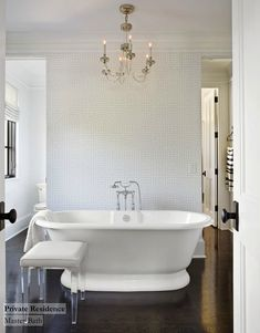 Fabulous bathroom with Jonathan Adler Greek Key Wallpaper in White. This bathroom also features a glass and polished nickel chandelier over freestanding bathtub with floor-mounted tub filler paired with upholstered lucite stool. Notice the dark stained oak wood floors.