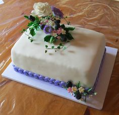 Fondant cake with ranunculus, roses, filler flowers and black berry